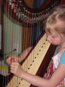 Kinderhände an der Harfe